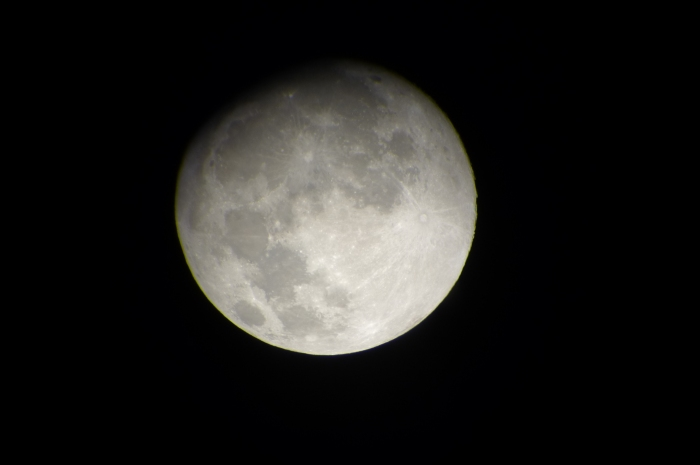 The mostly full moon. The top edge is eclipsed by the eyepiece lens.